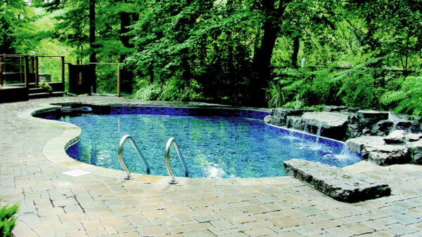 outdoor pool in the backyard and stone interlocking - stairs and railings