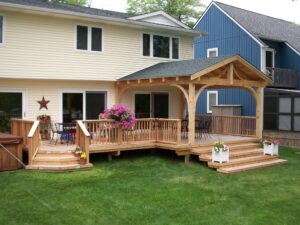 custom Deck with pergola next to blue house