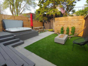 custom gray deck with a pool and outdoor fireplace -